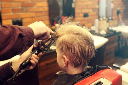 Hair cutting in a barbershop. A child, a boy, during a haircut at a barbershop.