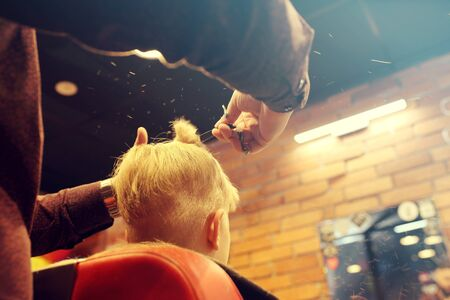 Professional hairdresser, fashionable men's hairstyle. A child, a boy, during a haircut at a barbershop. Archivio Fotografico