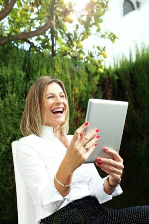 Smile and joy. Woman watching a funny movie on the tablet. Archivio Fotografico