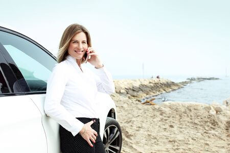 Tradesman woman talking on the phone based on the company car.Portrait of a young businesswoman woman talking on the phone