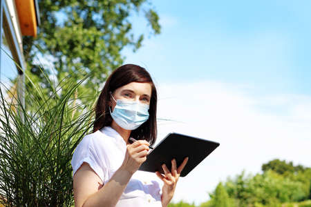 Remote work during an epidemic. A woman freelancer in a protective mask works in an urban space using a tablet.