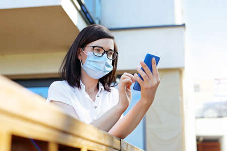 Video call. A woman in a protective mask is talking online on a mobile phone.