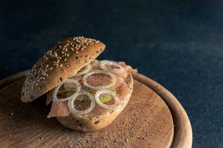 High-angle view of whole-grain bun with wild salmon, onion rings and slices of pear on wooden board and dark table