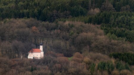 Small church in the middle of the bavarian forest surrounded by trees on an overcast day