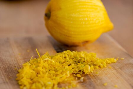 Close up of lemon zest with lemon in background lying on wooden board