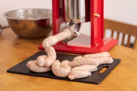 Making bavarian white sausages at home, chain of sausages lying on table
