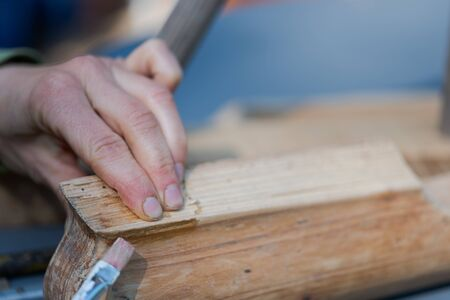 Human hands applying bone glue with brush on piece of old wooden furniture