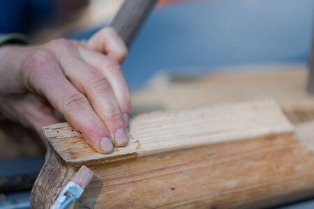 Mains humaines appliquant la colle d'os avec la brosse sur le morceau de vieux meubles en bois