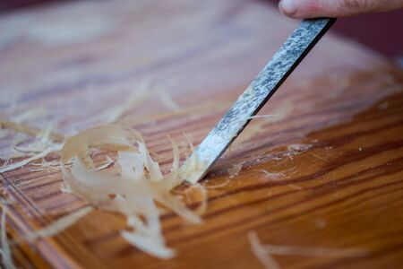 Scraping off old varnish of old wooden furniture with thin chisel