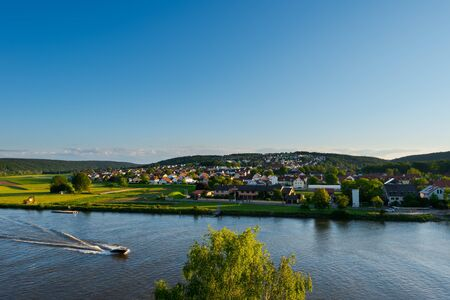 Overview of the bavarian village Sinzing near Regensburg with speed boat cruising on the danube river in golden afternoon light on clear summer day