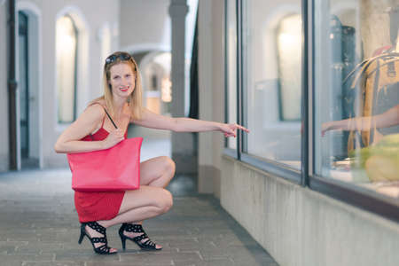 Full length portrait of young blond fashion-concious woman in red dress with big red shopping bag pointing at window of store while looking and smiling at camera in historic alley with old houses,