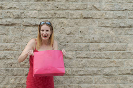 Young blond woman in red dress is happily laughing at camera while holding a red shopping bag and standing in front of gray brick wall