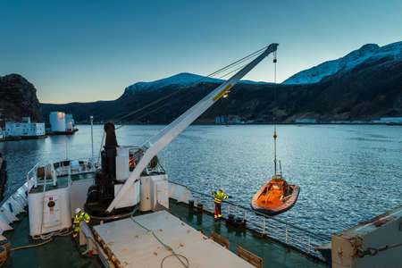 Unloading cargo with crane from freighter in the port of the city Maloy in Norway seen from cruise ship in early morning