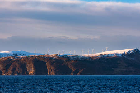 Wind farm on snow capped mountains on steep coast line of Norway seen from the ocean on sunny day with clouds