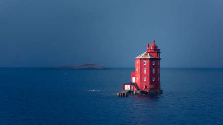 Famous red lighthouse Kjeungskjær in the middle of the ocean near the Norwegian coast in snow storm Stockfoto