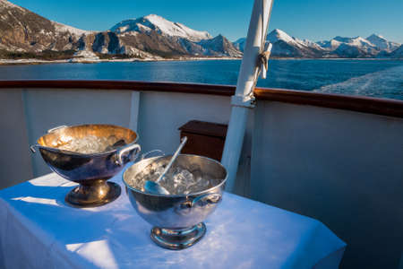 Two metal bowls with ice cubes standing on table on deck of cruise ship for the traditional ritual crossing-the-line ceremony 版權商用圖片