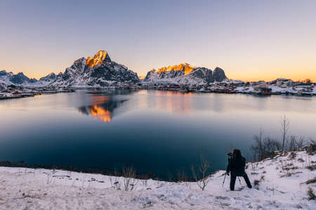 Landscape photographer with tripod seen from behind near the small fishing village Reine on the Lofoten islands in Norway in winter with steep snowcapped mountains and frozen lake during sunset