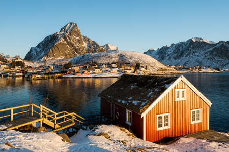 Renovated traditional red rorbu fishing hut on rocky coast near Reine on the Lofoten islands in Norway in winter with ocean and snow capped mountains in sunrise light