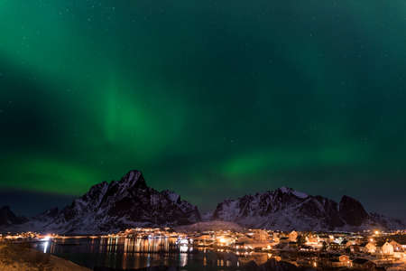 Dancing green polar lights over the village Reine on the Lofoten islands in Norway at night in winter with snow capped mountains