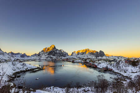The small fishing village Reine on the Lofoten islands in Norway in winter with steep snowcapped mountains and frozen lake during sunset