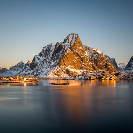 The small fishing village Reine on the Lofoten islands in Norway in winter with steep snowcapped mountains and frozen lake during sunrise