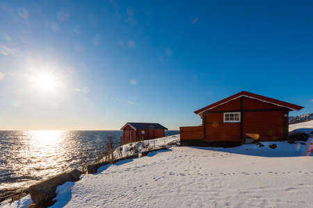 Sun flare on renovated traditional red rorbu fishing hut with empty racks for drying cod on the Lofoten islands in Norway in winter on the coast 版權商用圖片