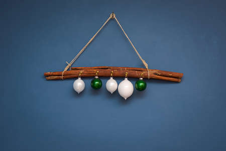 White and green christmas ornament balls hanging on hooks on big cinnamon stick on cord against blue painted wall
