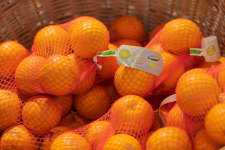 Regensburg, Germany - 2021 02 05: Mesh nets full of oranges of brand dennree lying in basket in organic super market with German label