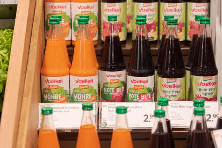 Regensburg, Germany - 2021 02 05: Bottles of different vegetable juices from brand Voelkel standing on display in organic super market with German label