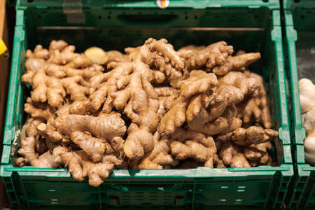 Unpacked loose ginger root bulbs in green plastic box on display in organic super market Banco de Imagens