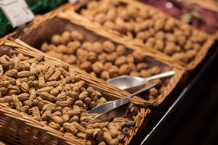 Unpacked peanuts and other nuts with shovels in baskets on display in organic super market