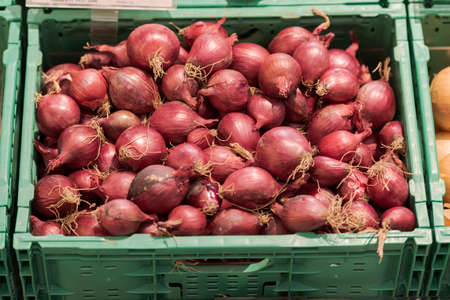 Unpacked loose red onions in green plastic box on display in organic super market