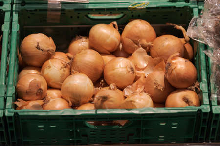 Unpacked loose onions in green plastic box on display in organic super market