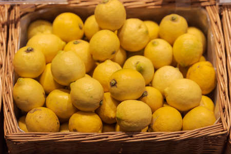 Unpacked organic lemons in basket on display in organic super market 版權商用圖片