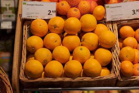 Regensburg, Germany - 2021 02 05: Unpacked organic oranges and clementines in basket with price tag on display in organic super market 新聞圖片