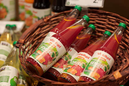 Regensburg, Germany - 2021 02 05: Bottles of vegetable juice from brand Voelkel with demeter certification lying in basket on display in organic super market with German label 新聞圖片