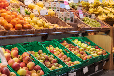 Regensburg, Germany - 2021 02 05: Various sorts of unpacked apples and other fruits in green plastic boxes and baskets on display in organic super market