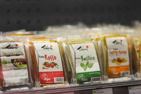 Regensburg, Germany - 2021 02 05: Refrigerated section with packaged various tofu flavors of brand Taifun behind glass doors on display in organic super market