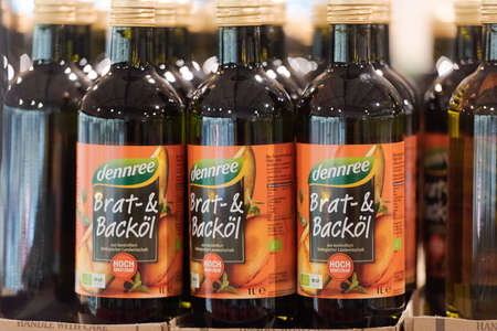 Regensburg, Germany - 2021 02 05: Bottles of brand dennree with oil for frying and baking standing on display in organic super market with German label