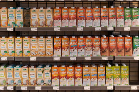 Regensburg, Germany - 2021 02 05: Shelves with cartons with soy, almond and oats drink of brands Natumi and Allos on display in organic super market