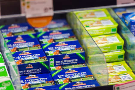 Regensburg, Germany - 2021 02 05: Refrigerated section with packs of butter of brands Berchtesgadener Land and dennree behind glass doors on display in german organic super market