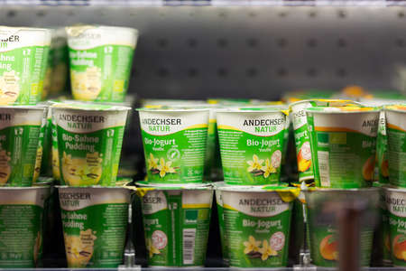Regensburg, Germany - 2021 02 05: Refrigerated section with various tastes of yoghurt in plastic cups of brand Andechser behind glass doors on display in organic super market 新聞圖片