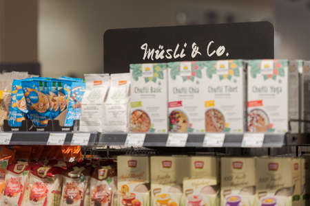 Regensburg, Germany - 2021 02 05: Shelf in aisle in german organic supermarket with sign meaning muesli and co.