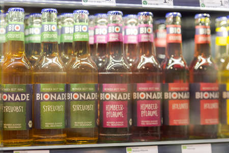 Regensburg, Germany - 2021 02 05: Refrigerated section with organic soft drink bottles of German brand Bionade behind glass doors on display in organic super market