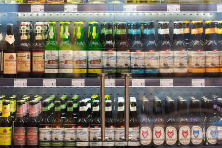 Regensburg, Germany - 2021 02 05: Refrigerated section with bottles of various German craft beer brands behind glass doors on display in organic super market