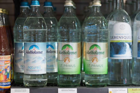 Regensburg, Germany - 2021 02 05: Glass bottles of mineral water of brand Adelholzener on shelf in german organic super market