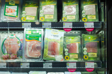 Regensburg, Germany - 2021 02 05: Refrigerated section with packs of various sliced ham and sausages of different brands behind glass doors on display in German organic super market 新聞圖片