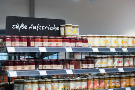 Regensburg, Germany - 2021 02 05: Shelf in aisle in german organic supermarket with sign meaning sweet spreads