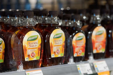 Regensburg, Germany - 2021 02 05: Glass bottles with maple syrup of brand dennree on shelf in german organic super market Editorial