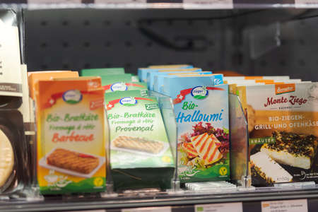 Regensburg, Germany - 2021 02 05: Refrigerated section with packs of grill cheese and halloumi of brand Züger behind glass doors on display in German organic super market Editorial
